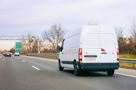 White Minivan on road. Mini van auto vehicle on driveway. European van transport logistics transportation. Auto with driver on highway.
