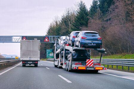 Camión transportador portador de coche en carretera. Transportista de vehículos automáticos en la calzada. Logística de transporte europea en el transporte de trabajo de transporte. Remolque de transporte pesado con conductor en carretera. Foto de archivo