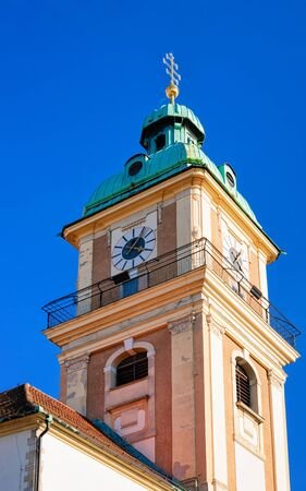 Belfry of John the Baptist Cathedral in Old city of Maribor, Slovenia. Church tower on Blue sky background. Tourism on Summer day. Christian Basilica with empty copy space. Religious architecture.