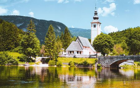 Scenery and Church of St John Baptist on Bohinj Lake, Slovenia. Nature in Slovenija. View of blue sky with clouds. Beautiful landscape in summer. Alpine Travel destination. Julian Alps mountains Stock Photo