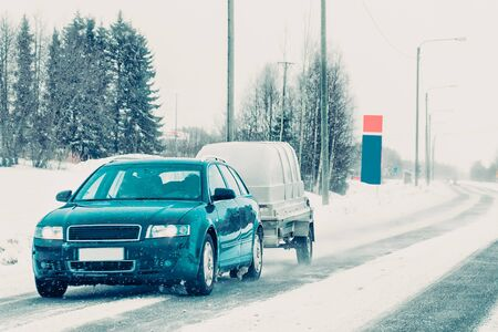 Car with trailer in road in Rovaniemi winter Lapland Finland