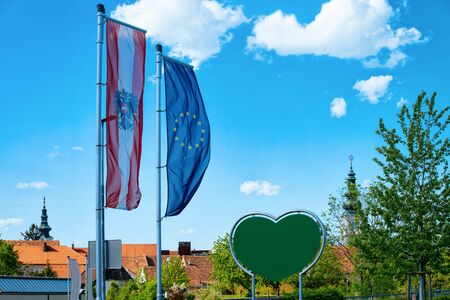Austrian and EU flags in Austria. Modern european empty green Traffic warning road sign - heart shape safety construction symbol. Street blank information concept. Transportation board frame. Stock fotó