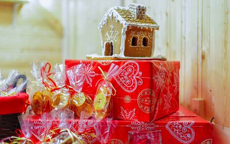 Gingerbread house among other cookies on Vilnius Christmas Market, Lithuania. It is one of the main Christmas symbols which can be decorated with various candies and ornaments.