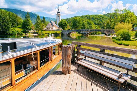 Touristic boat and wooden bench Bohinj Lake in Slovenia