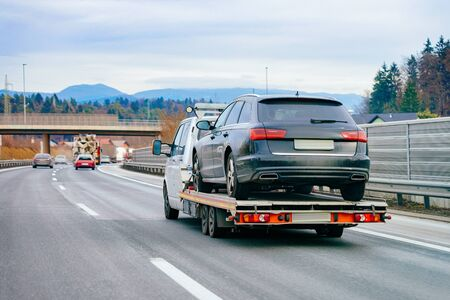Tow truck with car on warranty in road Stock fotó
