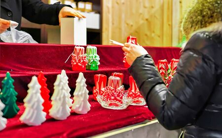 Colorful wax candles and seller on Vilnius Christmas Market new Stock Photo