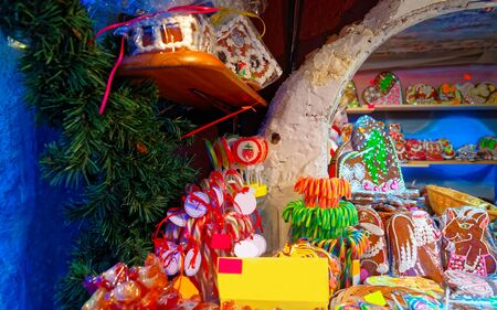 Candy canes and gingerbread hearts and houses displayed on a traditional Christmas market