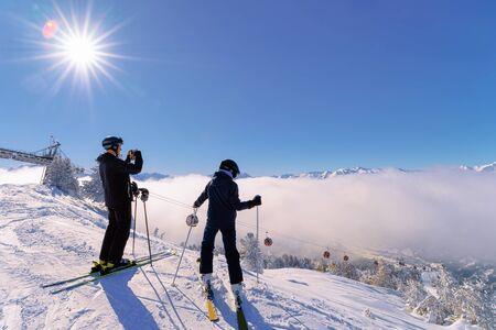 Menschen Skifahrer Skifahren und Fotografieren im Skigebiet Zillertal Arena in Tirol in Mayrhofen in Österreich im Winter Alpen. Skifahren in alpinen Bergen mit weißem Schnee und blauem Himmel. Verschneite Pisten. Sonnenschein.