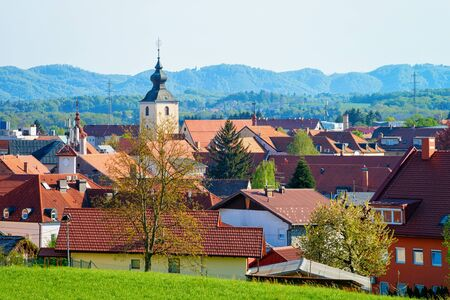 Cityscape with house roofs and Our Lady of the Seven Sorrows Church in Old center in Slovenska Bistrica near Maribor in Slovenia. South Styria in Slovenija. Bell tower of Cathedral in Slovenian town.