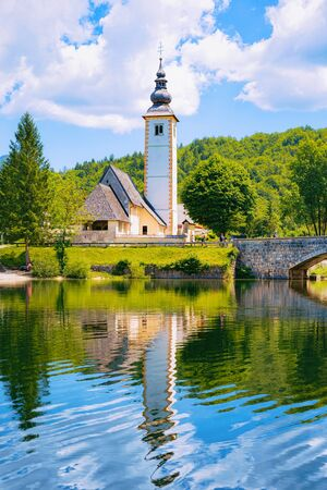 Scenery with Church of St John Baptist on Bohinj Lake in Slovenia. Nature in Slovenija. View of blue sky with clouds. Beautiful landscape in summer. Alpine Travel destination. Julian Alps mountains