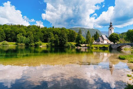 Scenery of Church of St John Baptist on Bohinj Lake of Slovenia. Nature in Slovenija. View of blue sky with clouds. Beautiful landscape in summer. Alpine Travel destination. Julian Alps mountains