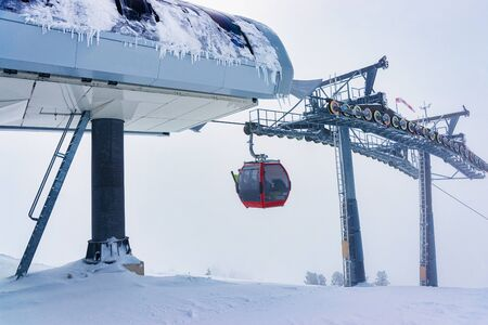 Red Cable car in cloudy Zillertal Arena ski resort in Tyrol in Mayrhofen in Austria in winter Alps. Chair lifts in Alpine mountains with white snow and blue sky. Downhill fun at Austrian snowy slopes 免版税图像