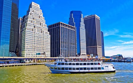 Ferry at Pier 17 and harbour of South Street Seaport with Skyline of Skyscrapers in Manhattan, New York City, America USA. American architecture building. Metropolis NYC. Cityscape. Hudson, East River