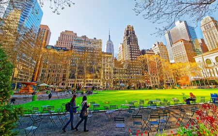 Tourists looking at Green Lawn in Bryant Park in Midtown Manhattan, New York, USA. United States of America. NYC, US. Skyline with skyscrapers and American cityscape.