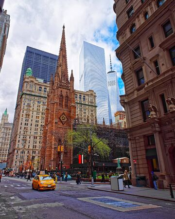 Street view on Trinity Church in Financial District of Lower Manhattan, New York of USA. Skyline and cityscape with skyscrapers at United States of America, NYC, US. American architecture. Wall Street
