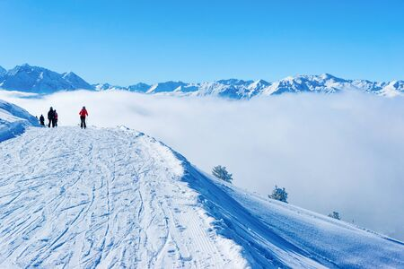 Skiers skiing in Zillertal Arena ski resort in clouds Austria