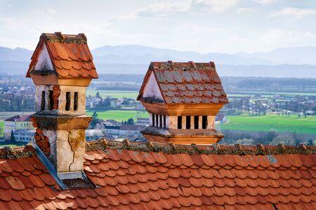 Red tile roof with chimneys in Ptuj Castle in Slovenia. Fragment of Architecture of Ptujski grad in Slovenija.