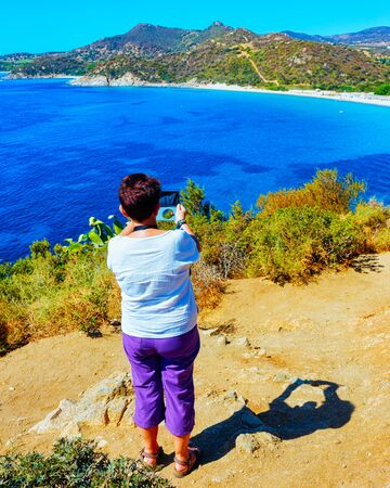 Senior woman taking photos of beach near Mediterranean Sea Villasimius reflex