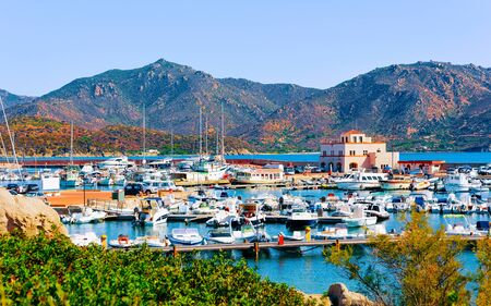 Old Sardinian Port and marina with ships at Mediterranean Sea in city of Villasimius in South Sardinia Island Italy in summer. Cityscape with Yachts and boats