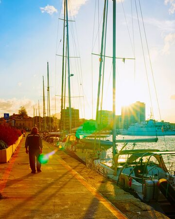 Atardecer en el puerto con reflejos de barcos de lujo de Olbia