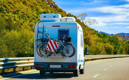 Rv cavaran with bicycles on road in Costa Smeralda Sardinia reflex