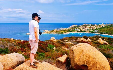 Mann und Landschaft mit felsiger Küste von Capo Testa in Santa Teresa Gallura am Mittelmeer auf der Insel Sardinien im Sommer Italien. Landschaft der Provinz Cagliari. Gemischte Medien.