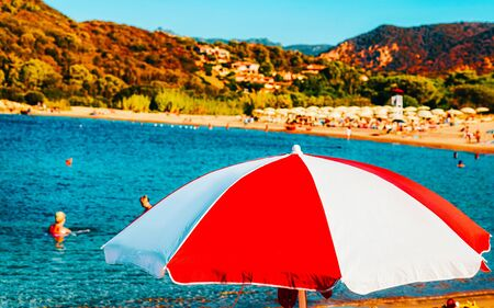 Landscape of Chia Beach with umbrellas and Blue Waters of the Mediterranean Sea in Province of Cagliari in South Sardinia in Italy. Scenery and nature. Mixed media.