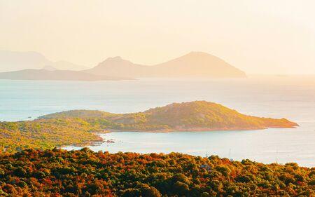 Scenery with Porto Rotondo at sunrise or sunset at Mediterranean Sea on Costa Smeralda. Porto Cervo in Sardinia Island in Italy in summer. Landscape on Sardegna. Sardinian Olbia province. Mixed media.