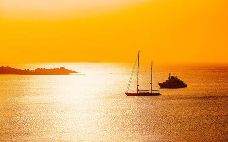 Sunrise or sunset with yachts at Porto Rotondo on Costa Smeralda at Mediterranean sea in Sardinia island of Italy. Boat in Sardegna in summer. Landscape of Olbia province. Mixed media. Zdjęcie Seryjne
