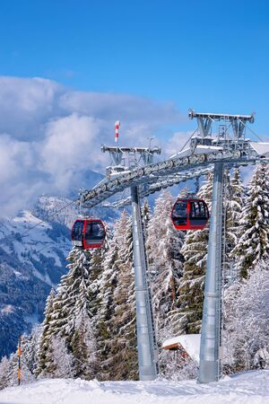 Red Cable cars at Zillertal Arena ski resort in Tyrol in Mayrhofen in Austria in winter Alps. Chair lifts in Alpine mountains with white snow and blue sky. Downhill fun at Austrian snowy slopes. Stock fotó