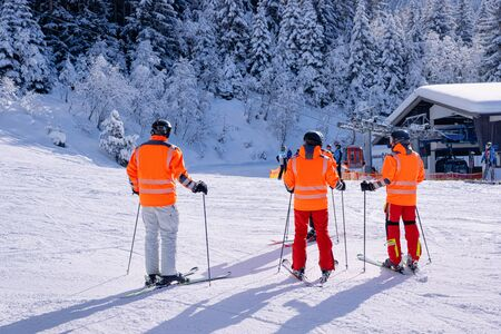Emergency rescue team in orange uniform on ski in Zillertal Arena ski resort in Tyrol in Mayrhofen in Austria in winter Alps. Rescuer response group in Alpine mountains with white snow and blue sky. Stock fotó