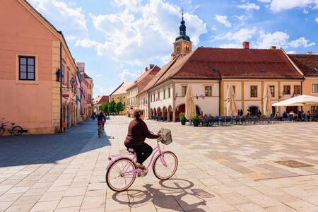 Senior woman on bicycle at Street cafes and restaurants on Town Hall on King Tomislav Square in Old city of Varazdin in Croatia. Cityscape of famous Croatian town in Europe in summer