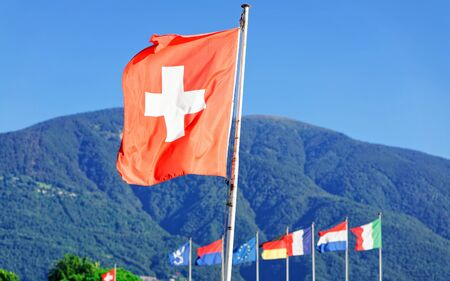Flags in Ascona, Ticino canton in Switzerland. Swiss Alps on the background. Mixed media.
