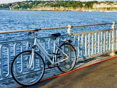 Bicycle at Promenade of Quai Fleuri at Geneva Lake in summer, Geneva, Switzerland. Mixed media. Foto de archivo