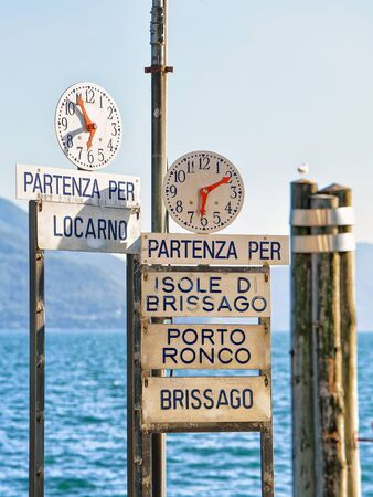 Clock at the Pier at the promenade at Ascona luxurious resort on Lake Maggiore, of Ticino canton in Switzerland. The lettering on the sings under the clocks are Names of towns and their piers on the Lake Maggiore, written In Italian. Mixed media.