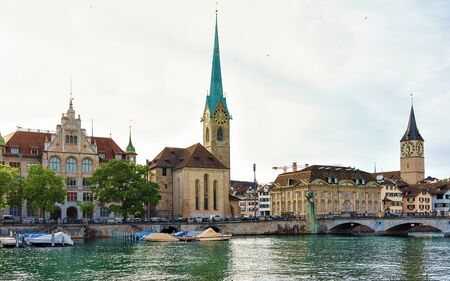 Fraumunster Church and Saint Peter and boats at Limmat River quay in the city center of Zurich, Switzerland. People on the background. Mixed media.