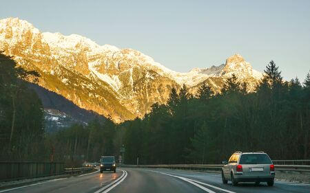 View of road with car at sunset in winter Switzerland. Switzerland is a country in Europe. Switzerland has a high mountain range, from the Alps to Jura mountains. Mixed media.