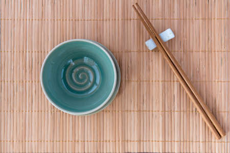Empty Bowl with Chopsticks on Bamboo Mat