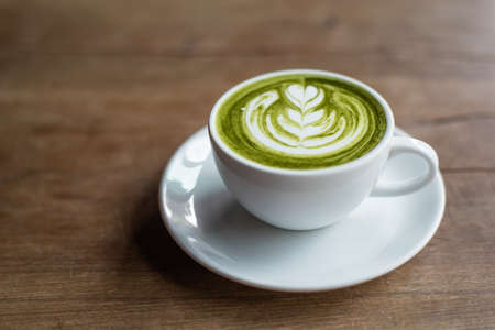 tea hot drink: matcha latte on wooden background
