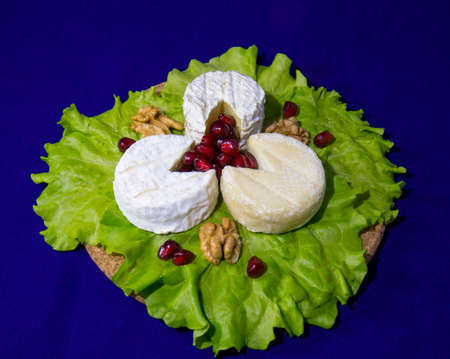 Cheese of three varieties on the plate with lettuce leaves, pomegranate seeds and walnuts (Saint-remy, Crottin d Eyubonne, Shayba) Stock Photo