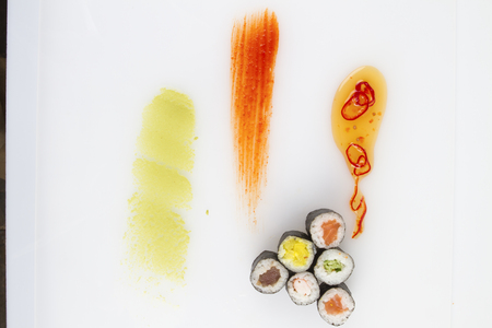 plating: sushi rolls and sauce on white background