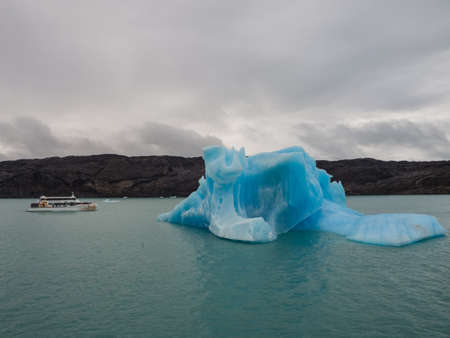 Iceberg and boat comparation in Lake Argentina in front of tha Upsala glacier Imagens - 108098377