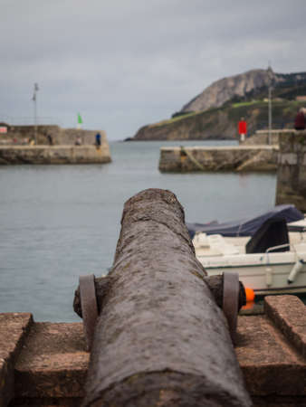 Ancient cannon in the harbor of the village of Mundaca in Vizcaya on a cloudy day, Spain Imagens