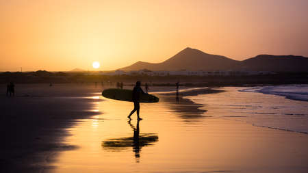 Silhouette of a Surfer on Famara beach at sunset, Canary Island