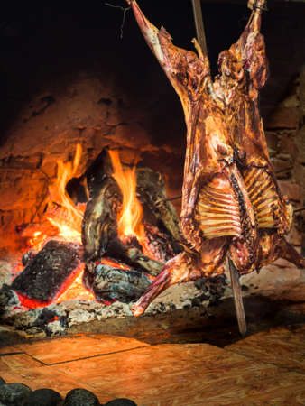 Lamb of Patagonia slowly roasted over the fire, typical dish of Chile and Argentina. Lamb to the post. Cordero al palo