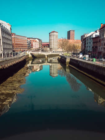 Puente de la Merced in Bilbao, reflections on the Ria de Bilbao on a sunny day, Basque Country Banco de Imagens