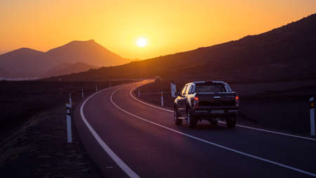 Car on a winding road driving towards sunset. Lanzarote