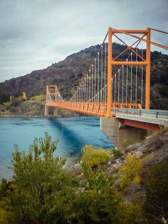 Red suspension bridge over the water runoff of General Carrera Lake, near Lake Bertrand, Puerto Tranquilo, Chile Chico, Aysen, Chile