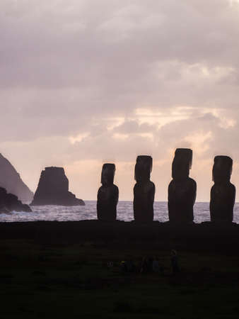 Sunrise at Ahu Tongariki with the motu at the back, silhouette of six of the fifthteen moais
