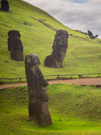 Moais statues in Rano Rarako volcano, easter Island. Buried moais in Rapa Nui Island, Chile Archivio Fotografico
